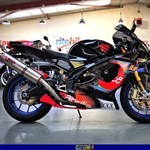 Production (Stock) Aprilia RSV Mille Models, a motorcycle parked on the side of a mountain a red and black Aprilia RSV Mille Sportbike parked in a room