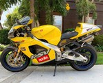 Production (Stock) Aprilia RSV Mille Models, a yellow motorcycle parked on the side of the road a yellow Aprilia RSV Mille Models Sportbike parked on the side of the road