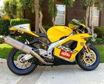 Production (Stock) Aprilia RSV Mille Models, a yellow motorcycle parked on the side of a road a yellow Aprilia RSV Mille Models Sportbike parked on the side of a road