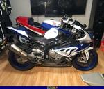 Production (Stock) BMW S1000RR, a motorcycle that is sitting in a room a BMW S1000RR Sportbike that is sitting in a room