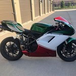 Production (Stock) Ducati 1098/1198, a green motorcycle parked on the side of a building a green Ducati 1098/1198 Sportbike parked on the side of a building
