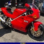 Production (Stock) Ducati 851/888 Superbike, a red and black motorcycle is parked on the side of a road a red and black Ducati 851/888 Superbike Sportbike is parked on the side of a road