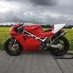 Production (Stock) Ducati 851/888 Superbike, a red and black motorcycle is parked on the side of the road a red and black Ducati 851/888 Superbike Sportbike is parked on the side of the road