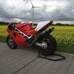 Production (Stock) Ducati 851/888 Superbike, a red motorcycle parked in a field a red Ducati 851/888 Superbike Sportbike parked in a field