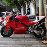 Production (Stock) Ducati 851/888 Superbike, a red motorcycle parked on the side of a road a red Ducati 851/888 Superbike Sportbike parked on the side of a road