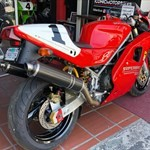 Production (Stock) Ducati 851/888 Superbike, a red and black motorcycle is parked on the side of a building a red and black Ducati 851/888 Superbike Sportbike is parked on the side of a building