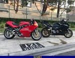 Production (Stock) Ducati 900cc Models, a red and black Ducati 900cc Models is parked on the side of a building