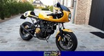 Production (Custom) Ducati 900cc Models, a black and yellow motorcycle parked on the side of a building a black and yellow Ducati 900cc Models parked on the side of a building