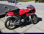 Production (Stock) Ducati 900cc Models, a red and black motorcycle is parked on the side of a road a red and black Ducati 900cc Models Sportbike is parked on the side of a road