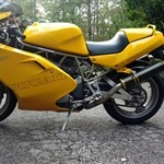 Production (Stock) Ducati 900cc Models, a black and yellow motorcycle parked on the side of a road a black and yellow Ducati 900cc Models Sportbike parked on the side of a road