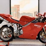 Production (Stock) Ducati 916/996/998, a red motorcycle parked on the side of a building a red Ducati 916/996/998 Sportbike parked on the side of a building