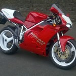 Production (Stock) Ducati 916/996/998, a motorcycle parked on the side of a road a Ducati 916/996/998 Sportbike parked on the side of a road