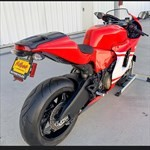 Production (Stock) Ducati Desmosedici, a red and black motorcycle is parked on the side of a road a red and black Ducati Desmosedici Sportbike is parked on the side of a road