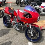 Production (Stock) Ducati Monster Models, a red motorcycle parked in a parking lot a red Ducati MH900e Sportbike parked in a parking lot