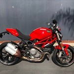 Production (Stock) Ducati Monster Models, a red and black motorcycle parked on the side of a road a red and black Ducati Monster Models Sportbike parked on the side of a road