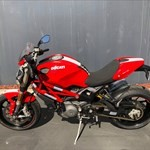 Production (Stock) Ducati Monster Models, a red and black motorcycle is parked on the side of a road a red and black Ducati Monster Models Sportbike is parked on the side of a road