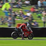 Misc. Racing Ducati Panigale V4, a close up of a man riding a motorcycle on a track a close up of a man riding a 2019 Ducati Panigale V4 Sportbike on a track