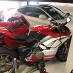 Production (Stock) Ducati Panigale V4, a red motorcycle parked in a parking lot a red Ducati Panigale V4 Sportbike parked in a parking lot