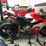 Production (Stock) Ducati Panigale V4, a red and black motorcycle is parked on the side of a building a red and black Ducati Panigale V4 Sportbike is parked on the side of a building