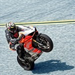 Stunts Ducati Panigale V4, a man riding a motorcycle next to a body of water a man riding a Ducati Panigale V4 Sportbike next to a body of water