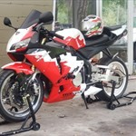 Production (Custom) Honda CBR600RR, a red and black motorcycle parked in a parking lot a red and black Honda CBR600RR Sportbike parked in a parking lot