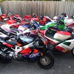 Production (Stock) Honda CBR900RR, a red motorcycle parked in a parking lot a red Honda CBR900RR Sportbike parked in a parking lot