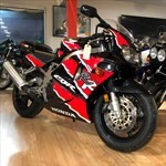 Production (Stock) Honda CBR900RR, a red and black motorcycle is parked on the side of a building a red and black Honda CBR900RR Sportbike is parked on the side of a building
