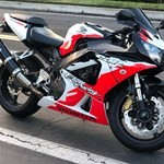 Production (Stock) Honda CBR929RR/CBR954RR, a red and black motorcycle parked on the side of a road a red and black Honda CBR 929/954 RR Sportbike parked on the side of a road