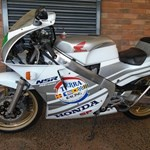 Production (Stock) Honda NSR250, a motorcycle parked in front of a brick building