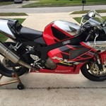 Production (Stock) Honda RC51, a red and black motorcycle is parked on the side of a road a red and black Honda RC51 Sportbike is parked on the side of a road