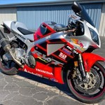 Production (Stock) Honda RC51, a motorcycle parked on the side of a building a Honda RC51 Sportbike parked on the side of a building
