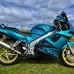 Production (Stock) Honda VFR Models, a motorcycle parked on the side of a road a blue and green Honda VFR Models Sportbike parked on a grassy field