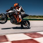 Production (Stock) KTM Duke Series, a man flying through the air while riding a motorcycle down a dirt road a man flying through the air while riding a KTM Duke Series Sportbike down a dirt road