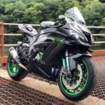 Production (Custom) Kawasaki Ninja ZX-10R, a green motorcycle parked on the side of the road a green Kawasaki Ninja ZX-10R Sportbike parked on the side of the road