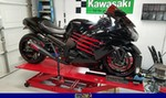 Production (Custom) Kawasaki Ninja ZX-14R, a red and black motorcycle is parked on the side of a building a red and black Kawasaki Ninja ZX-14 is parked on the side of a building