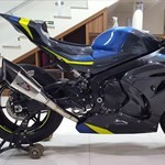 Production (Stock) Suzuki GSX-R1000, a motorcycle is parked in front of a blue wall a Suzuki GSX-R1000 Sportbike is parked in front of a blue wall