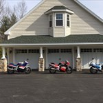 Production (Stock) Suzuki GSX-R750, a motorcycle parked in a parking lot in front of a house a Suzuki GSX-R750 Sportbike parked in a parking lot in front of a house
