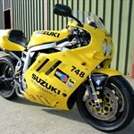 Production (Stock) Suzuki GSX-R750, a black and yellow motorcycle parked on the side of a road a black and yellow Suzuki GSX-R750 Sportbike parked on the side of a road