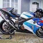 Production (Stock) Suzuki TL1000R/TL1000S, a blue and white motorcycle parked on the side of a building a blue and white Suzuki TL1000R/TL1000S Sportbike parked on the side of a building