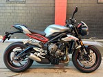 Production (Stock) Triumph Speed Triple, a red and black 2019 Triumph Speed Triple sportbike parked in front of a brick building