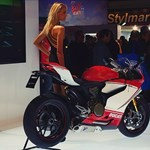 Women Ducati 1199/1299 Panigale, 2012 Ducati 1199 Panigale a person sitting on a 2012 Ducati 1199/1299 Panigale sportbike on display
