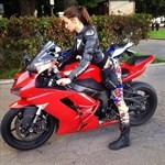 Women Kawasaki Ninja ZX-6R, kawasaki zx 6r dainese girl a red and black Kawasaki ZX-6 and ZZR600 sportbike is parked on the side of a road