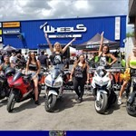 Women Multiple Multiple (Multiple), a group of people standing around a motorcycle