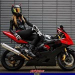 Women Suzuki GSX-R50, a red and black motorcycle is parked on the side of a building a red and black Suzuki GSX-R50 Sportbike is parked on the side of a building