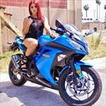 Women Kawasaki Ninja 250/300, a person in a blue motorcycle parked on the side of a road a person in a blue Kawasaki Ninja 250/300 Sportbike parked on the side of a road