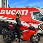 Women Ducati Panigale V4, a red motorcycle parked in a parking lot a red Ducati Panigale V4 Sportbike parked in a parking lot