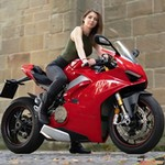 Women Ducati Panigale V4, a red and black motorcycle is parked on the side of a building a red and black Ducati Panigale V4 Sportbike is parked on the side of a building