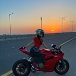 Women Ducati 1199/1299 Panigale, a motorcycle parked on the side of a road a Ducati 1199/1299 Panigale Sportbike parked on the side of a road
