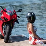 Women Ducati Panigale V4, a person riding a motorcycle next to a body of water a person riding a Ducati Panigale V4 Sportbike next to a body of water