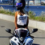 Women Yamaha YZF-R6, a person wearing a helmet riding a motorcycle on the side of a road a person wearing a helmet riding a Yamaha YZF-R6 Sportbike on the side of a road